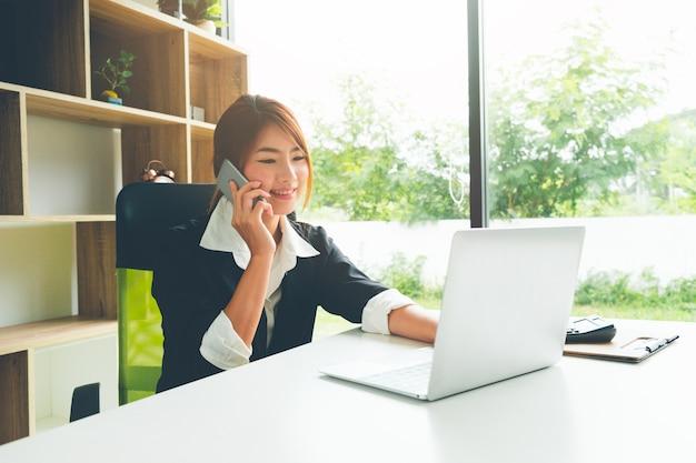 Schöne geschäftsfrau, die auf dem mobiltelefon arbeitet mit laptop und taschenrechner spricht