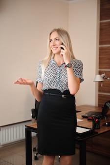 Schöne geschäftsfrau, die auf handy spricht. junge weibliche modellarbeit mit verkäufen im büro.