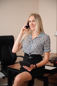 Schöne geschäftsfrau, die auf handy spricht. junge weibliche modellarbeit mit verkäufen im hellen büro.