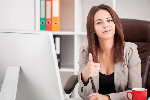 Schöne geschäftsfrau, die auf laptop schreibt