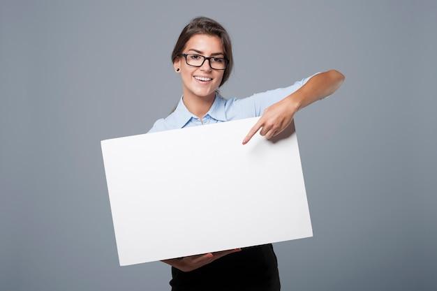Schöne geschäftsfrau, die auf leerem whiteboard zeigt