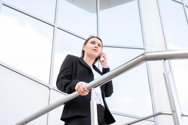 Schöne geschäftsfrau, die auf mobiltelefon beim gehen im freien spricht