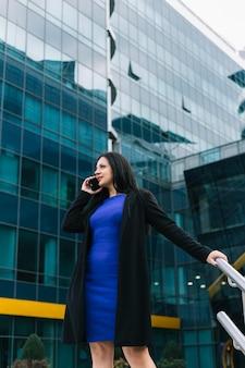 Schöne geschäftsfrau, die auf smartphone vor gebäude spricht