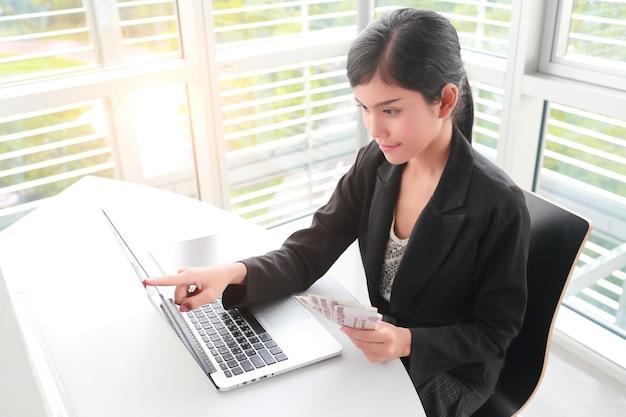 Schöne geschäftsfrau, die banknoten mit laptop-computer zeigt und hält