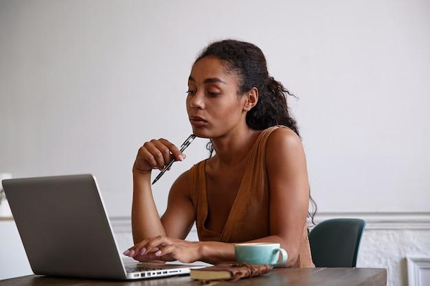 Schöne geschäftsfrau, die bericht über ihren stift in der hand vorbereitet und ihn auf ihr kinn stützt, kaffee trinkt und ernsthaft auf den monitor schaut