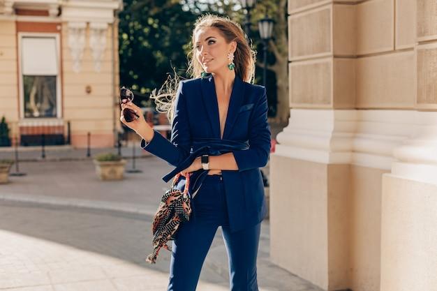 Schöne geschäftsfrau, die blaue jacke in der sexy luxusart gehenden straße trägt