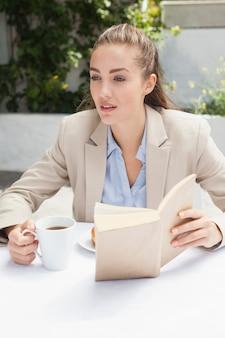 Schöne geschäftsfrau, die ein kaffeelesebuch hat