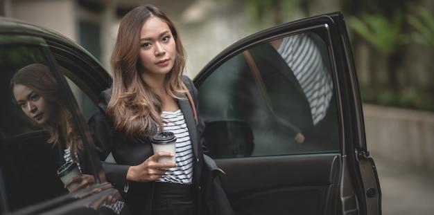 Schöne geschäftsfrau, die ein modernes luxusauto beim halten einer kaffeetasse verlässt