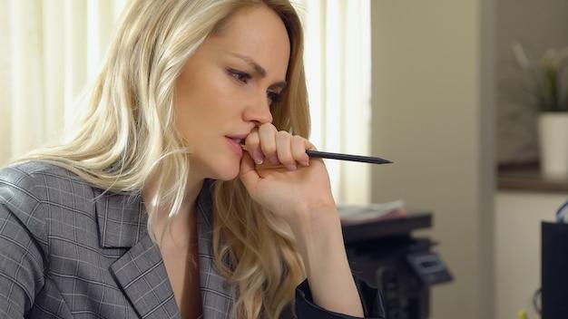Schöne geschäftsfrau, die ihren bleistift im büro beißt.