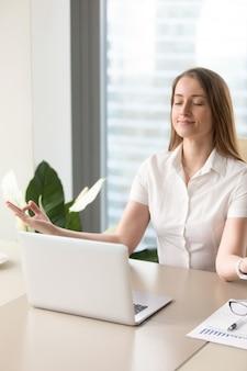 Schöne geschäftsfrau, die im büro meditiert