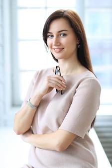 Schöne geschäftsfrau, die im innenbüro aufwirft
