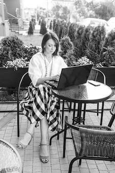 Schöne geschäftsfrau, die im stadtcafé sitzt und mit ihrem laptop arbeitet. schwarzweiss-bild