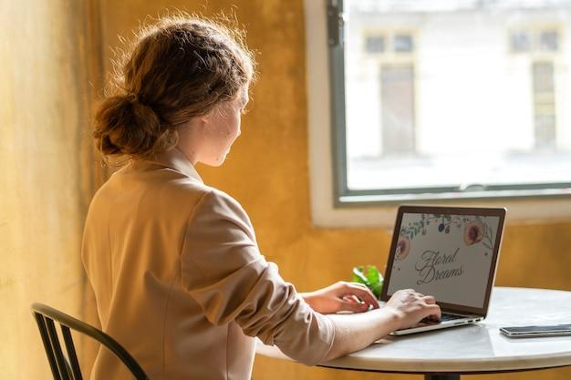 Schöne geschäftsfrau, die in einem café an ihrem laptop arbeitet