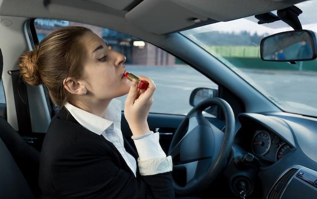 Schöne geschäftsfrau, die kosmetik beim autofahren anwendet