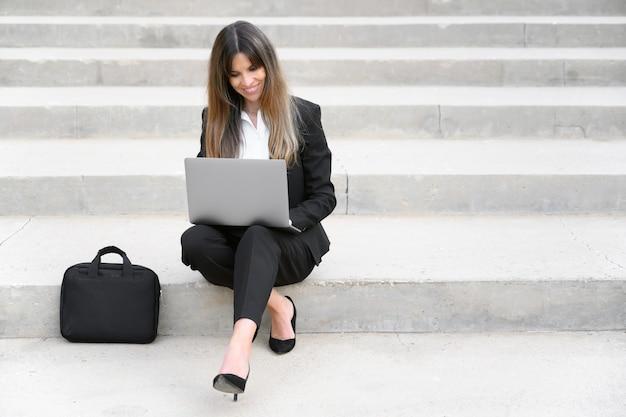 Schöne geschäftsfrau, die laptop beim sitzen auf treppen im freien verwendet