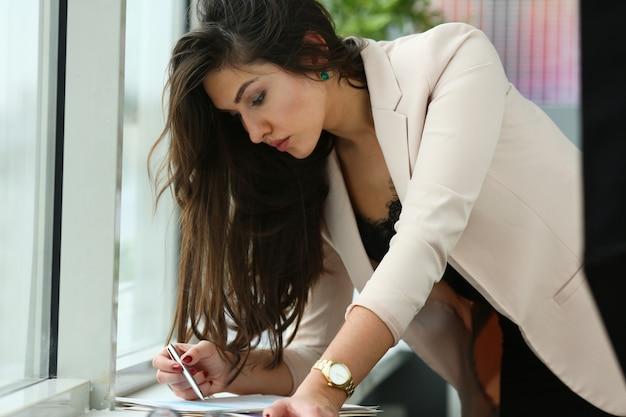 Schöne geschäftsfrau, die mit dokumenten im büro arbeitet