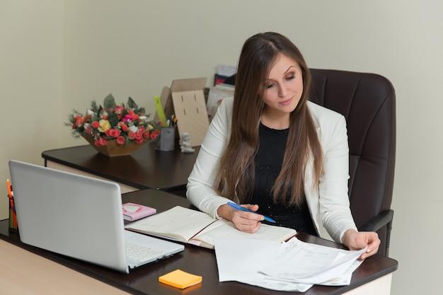 Schöne geschäftsfrau, die mit dokumenten im büro, arbeitsplatz arbeitet.