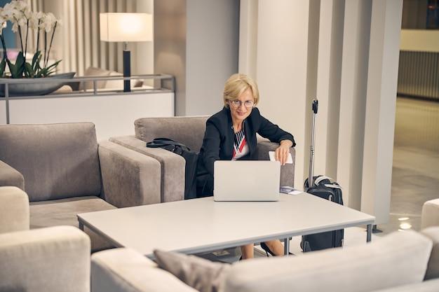 Schöne geschäftsfrau, die mit notebook am tisch sitzt und smartphone hält, während sie auf ihren flug in der halle wartet
