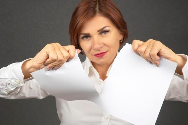 Schöne geschäftsfrau, die weißes papier in zwei hälften zerreißt