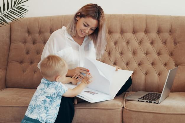 Schöne geschäftsfrau, die zu hause arbeitet. multitasking-, freiberufler- und mutterschaftskonzept