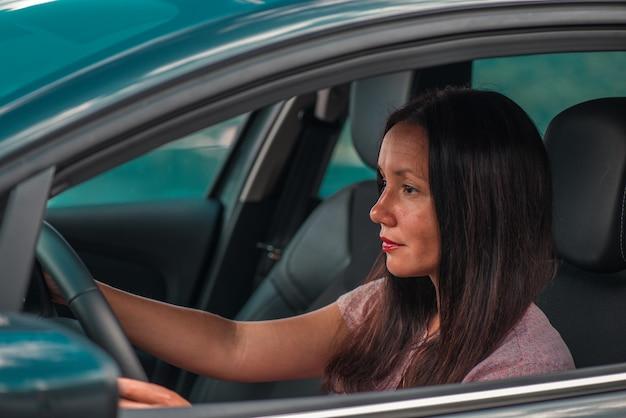 Schöne geschäftsfrau fährt ein auto. nahansicht.