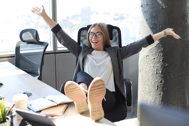 Schöne geschäftsfrau feiert triumph im geschäft im büro mit erhobenen händen.