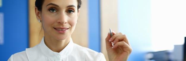 Schöne geschäftsfrau im weißen hemd halten stift mit dokument in ihrer hand und lächeln. im hintergrund ist arbeitsplatz im büro.