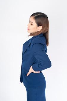 Schöne geschäftsfrau in den blauen klagenrückenschmerzen auf weißem hintergrund