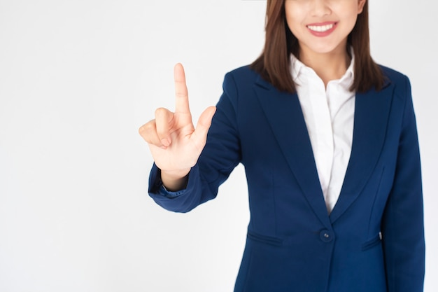 Schöne geschäftsfrau in der blauen klage berührt virtuellen bildschirm auf weißem hintergrund