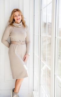 Schöne geschäftsfrau in einem eleganten kleid steht nahe am fenster im sonnenlicht.