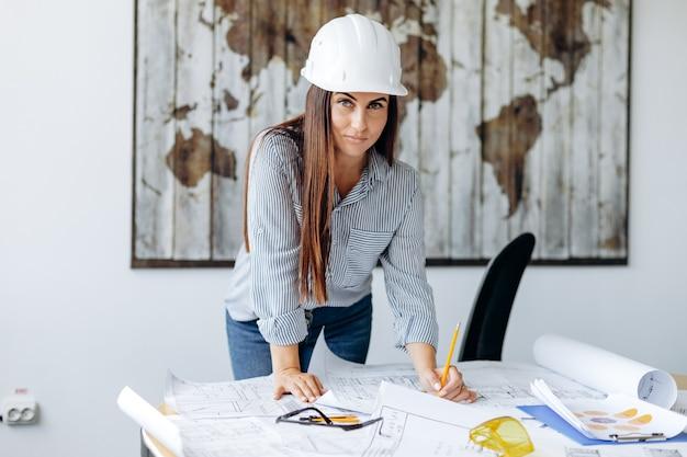 Schöne geschäftsfrau in einem helm im büro