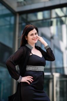 Schöne geschäftsfrau in einem schwarzen kleid.