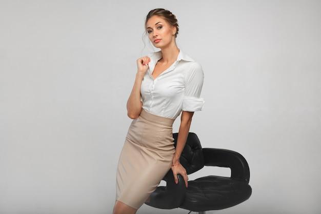 Schöne geschäftsfrau in einem weißen bürohemd, das auf einem barhocker des schwarzen leders sich lehnt