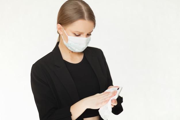 Schöne geschäftsfrau in einer medizinischen virusschutzmaske reinigt ihr telefon mit antibakteriellen tüchern. vorsichtsmaßnahmen gegen pandemien