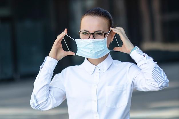 Schöne geschäftsfrau, junges mädchen, das medizinische schutzmaske auf ihrem gesicht, im weißen hemd in den gläsern im freien, gesundheitswesen am arbeitsplatz, arbeit, büro aufsetzt. coronavirus, virus, epidemie, covid-19-konzept