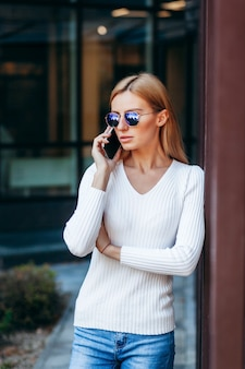 Schöne geschäftsfrau mit brille und telefon auf straßenhintergrund