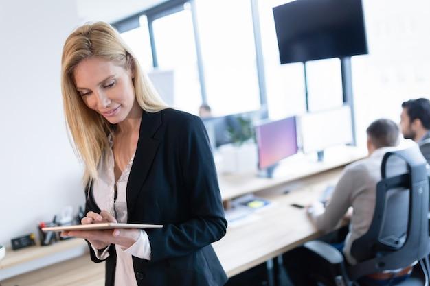 Schöne geschäftsfrau mit digitalem tablet im modernen büro