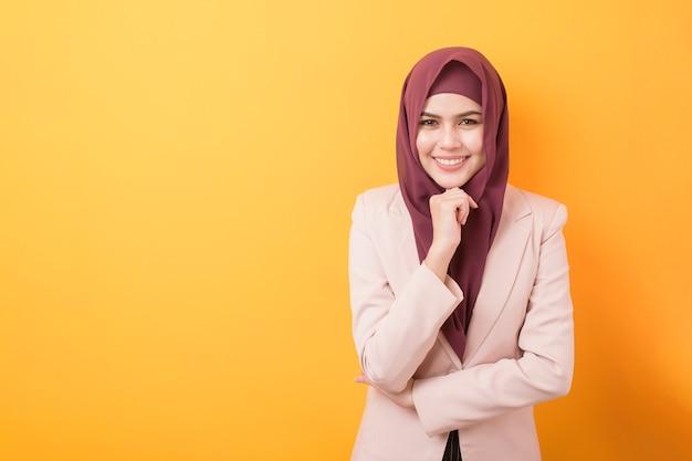 Schöne geschäftsfrau mit hijab-porträt auf gelbem hintergrund