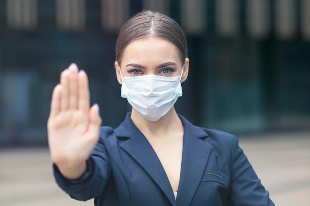 Schöne geschäftsfrau mit medizinischer schutzmaske auf ihrem gesicht
