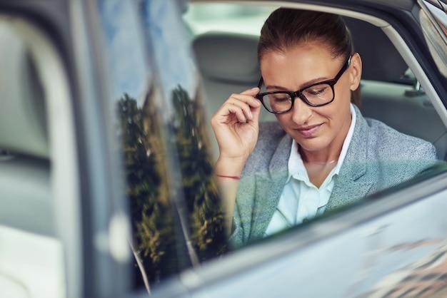 Schöne geschäftsfrau mittleren alters, die ihre brille beim sitzen auf dem rücksitz im taxi anpasst