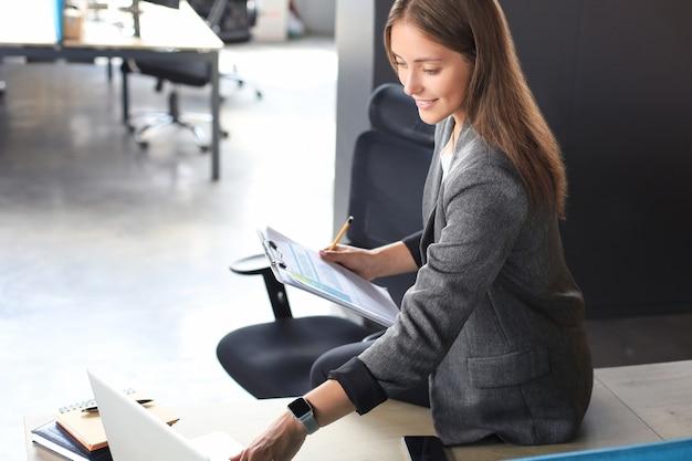 Schöne geschäftsfrau prüft dokumente während der arbeit im büro.