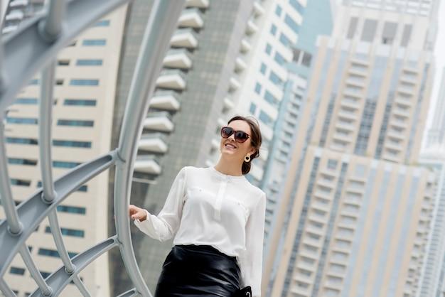 Schöne geschäftsfrau, schicke kleider, die die promenade in einer großen stadt entlang gehen.