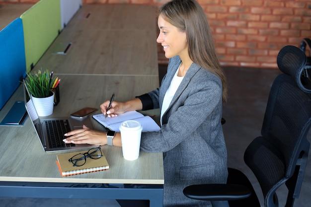 Schöne geschäftsfrau schreibt etwas auf, während sie im schreibtisch sitzt.