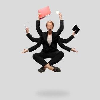 Schöne geschäftsfrau sekretärin multiarmed manager schwebend isoliert auf grauem studiohintergrund
