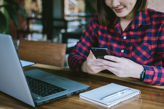 Schöne geschäftsfrau sind beschäftigt, an laptop und smartphone arbeitend und arbeiten online an schreibtisch.