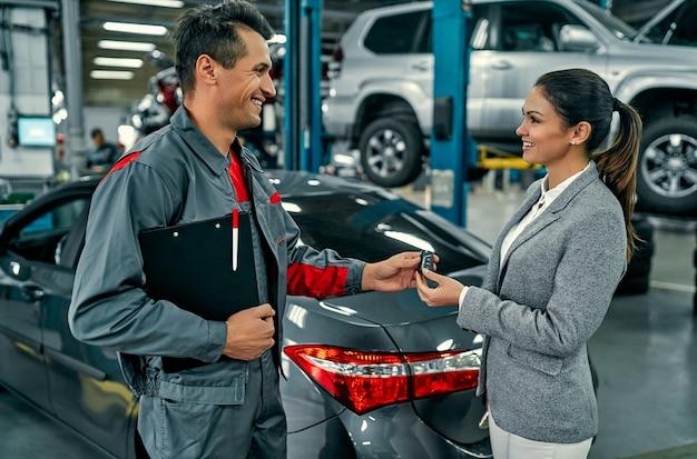 Schöne geschäftsfrau und autowerkstatt besprechen die arbeit und geben schlüssel. autoreparatur und wartung.