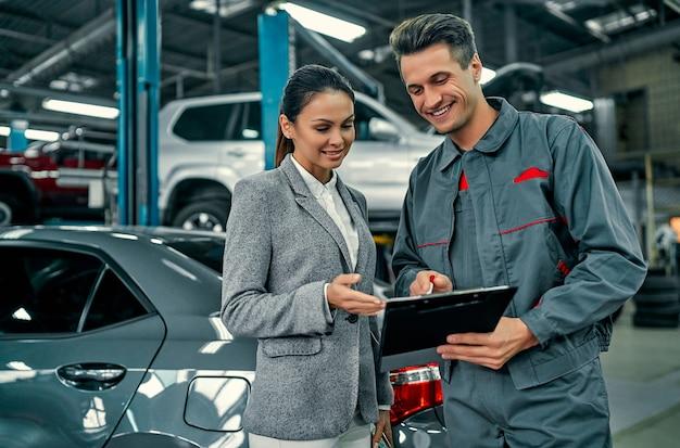 Schöne geschäftsfrau und autowerkstatt besprechen die arbeit und unterschreiben dokumente. autoreparatur und wartung.