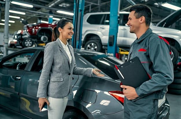 Schöne geschäftsfrau und autowerkstatt diskutieren die arbeit. autoreparatur und wartung.