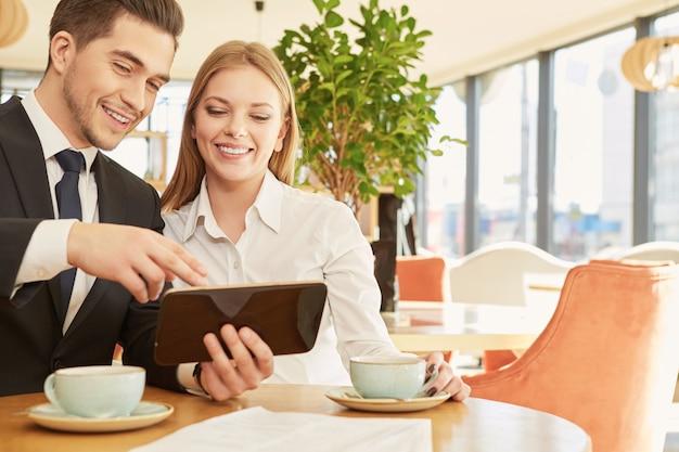 Schöne geschäftsfrau und ihr männlicher kollege, die projekte über frühstück am café bespricht