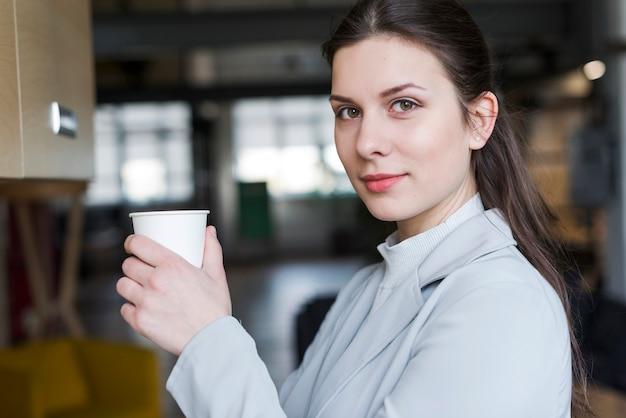 Schöne geschäftsfrau, welche die wegwerfkaffeetasse betrachtet kamera hält